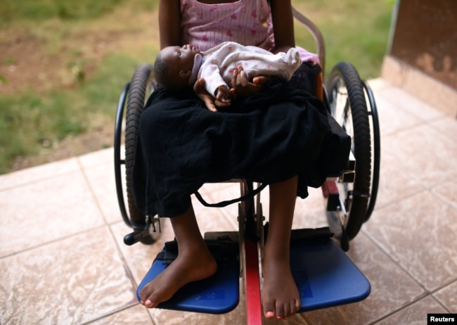 FILE - A five-year-old girl poses with her doll as she sits in her wheelchair in the courtyard of the Aberdeen Women's Center, one year after a sexual assault that her family says left her paralyzed, in Freetown, Sierra Leone, Feb. 7, 2019.