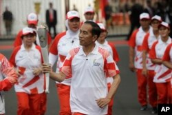 """FILE - Indonesian President Joko """"Jokowi"""" Widodo, center, holds the Asian Games torch as he runs during an independence day ceremony at Merdeka Palace in Jakarta, Indonesia, Aug. 17, 2018."""