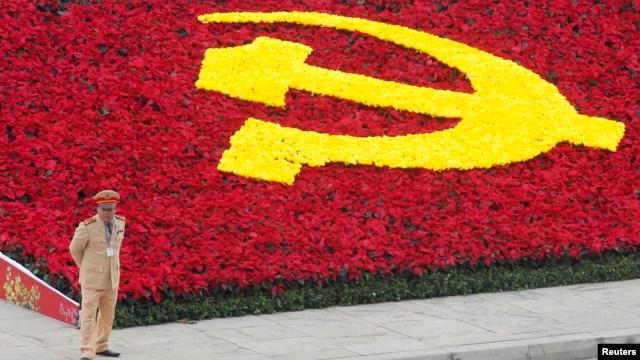 Một cảnh sát đứng bên cạnh biểu tượng đảng Cộng sản tại Trung tâm Hội nghị Quốc gia.