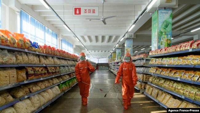 2021年10月20日,朝鲜首都平壤一家百货店工作人员在喷洒预防新型冠状病毒的消毒剂。(法新社)