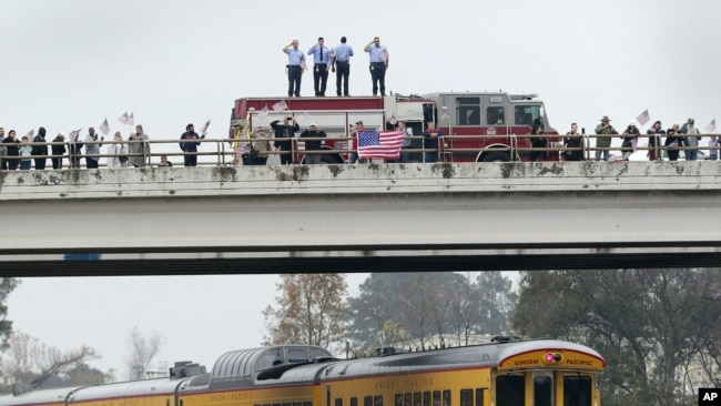 En un paso elevado, los bomberos saludan, junto con otros asistentes, el tren que lleva el cuerpo del expresidente George H.W. Bush.