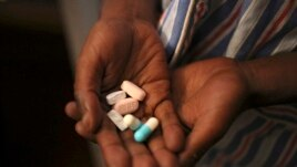 Nine-year-old Tumelo shows off antiretroviral (ARV) pills before taking his medication at Nkosi's Haven, south of Johannesburg, South Africa, Nov. 28, 2014. Seven million people in the country are currently living with the HIV virus.
