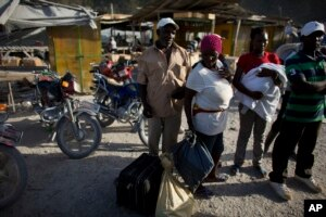 Haitian migrants just deported from Dominican Republic stand on the Haitian side of the border unsure what to do next, in Malpasse, Haiti, June 17, 2015.