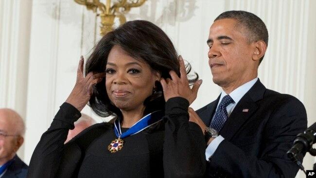 """Oprah Winfrey ki t ap resevwa """"Meday Prezidansyèl de la Libète a"""" (Presidential Medal of Freedom Award) nan men Prezidan Barack Obama nan yon seremoni ki te dewoule nan La Mezon Blanch nan Washington nan dat 20 novanm 2013."""