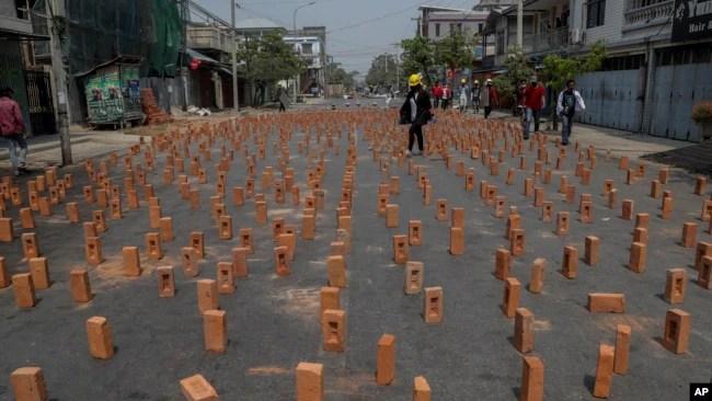 反对政变的抗议者走在缅甸曼德勒布满砖块路障的街头。(2021年3月10日)