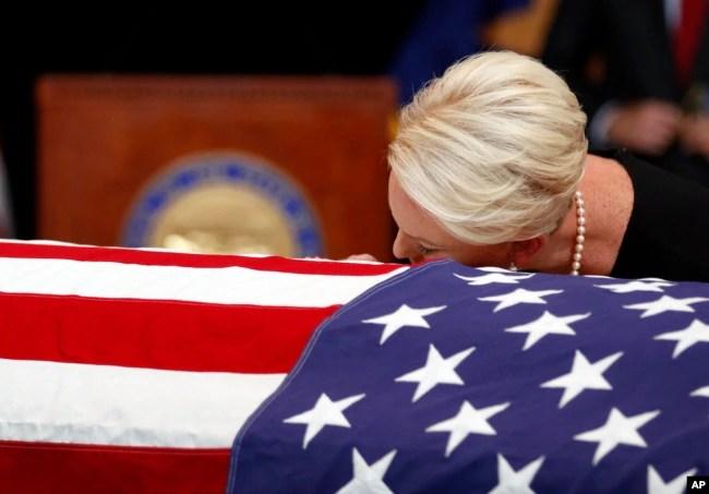 Cindy McCain, esposa del senador John McCain, apoya la cabeza sobre el ataúd durante el servicio recordatorio en Phoenix, Arizona, el miércoles, 29 de agosto de 2018.
