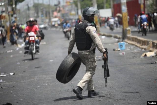 Un oficial de la Policía Nacional de Haití saca un neumático de una barricada en una calle de Puerto Príncipe, Haití, el 8 de julio de 2018. REUTERS / Andres Martinez Casares.