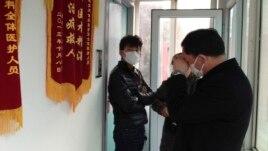 Bạn bè của bà Tào đứng bên ngoài phòng điều trị cho bà bởi vì họ không được phép vào trong, Bắc Kinh, 1/3/2014.