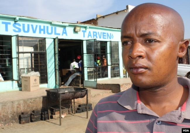 "Community health care worker Brown Lekekela stands outside a tavern in a township in South Africa, where young women often meet older men with whom they have dangerous ""transactional"" sexual relationships. (D. Taylor/VOA)"