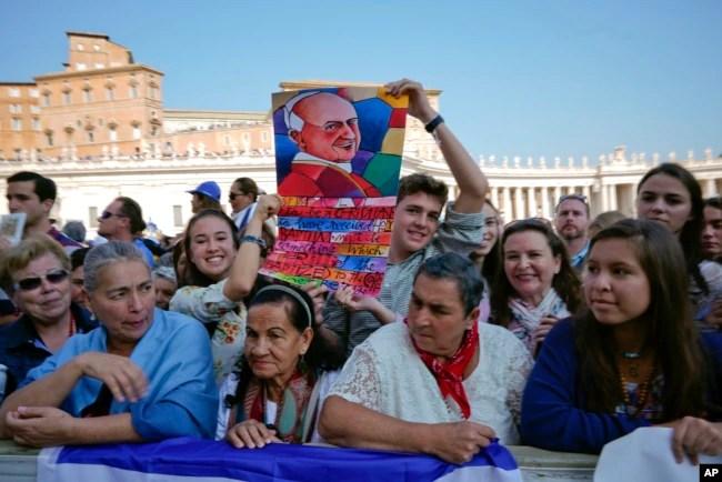 Fieles en El Vaticano siguen la ceremonia de canonización de dos de las más importantes figuras de la Iglesia Católica en el Siglo XX, el asesinado arzobispo salvadoreño Óscar Romero y el Papa Paulo VI, el domingo 14 de octubre de 2018. Otros cinco beatos también fueron elevados a la santidad.