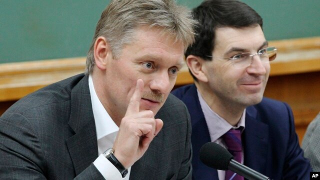 FILE - Russian President Vladimir Putin's spokesman Dmitry Peskov, left, speaks during a meeting in Moscow, Russia.