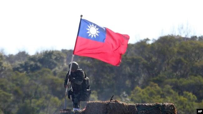 资料照:一名台湾士兵手举台湾旗帜参加新竹举行的军演模拟反击中国军队攻台。(2021年1月19日)