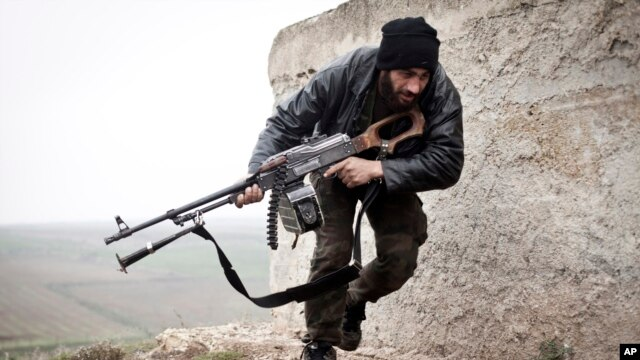 FILE - A Free Syrian Army fighter takes cover during fighting in Azaz, Syria, May 8, 2015.