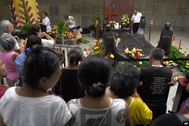 Fieles rezan frente a la tumba del arzobispo de El Salvador, Óscar Arnulfo Romero, en la catedral metropolitana de San Salvador, el 13 de octubre de 2018, un día después de que el asesinado arzobispo fuera elevado a la santidad junto con el papa Paulo VI y otros cinco beatos.