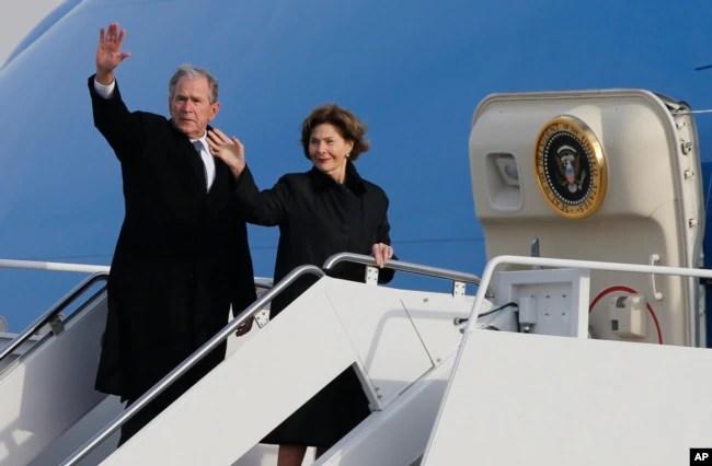 El expresidente George W. Bush saluda junto con a esposa, Laura Bush, desde el avión en el que acompaña el cuerpo de su padre el expresidente George H.W. Bush tras ceremonias de honor en Washington, de regreso a Texas para su último servicio funeral y entierro. Dic. 5 de 2018.