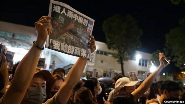 支持者在6月24日凌晨聚集在香港苹果日报总部外,举起最后一期的《苹果日报》并高呼支持苹果的口号 (美国之音粤语组听众郑先生)