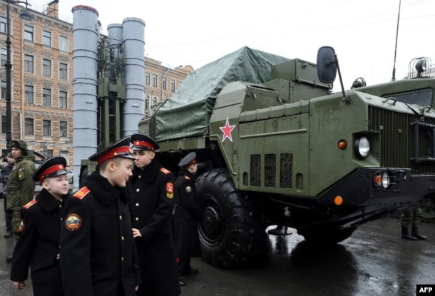 FILE – Russian cadets pass an S-300 surface-to-air missile system during a military exhibition in St. Petersburg, Feb. 20, 2015. Russia announced later that year that it would deliver missile systems that Iran had contracted for in 2007.