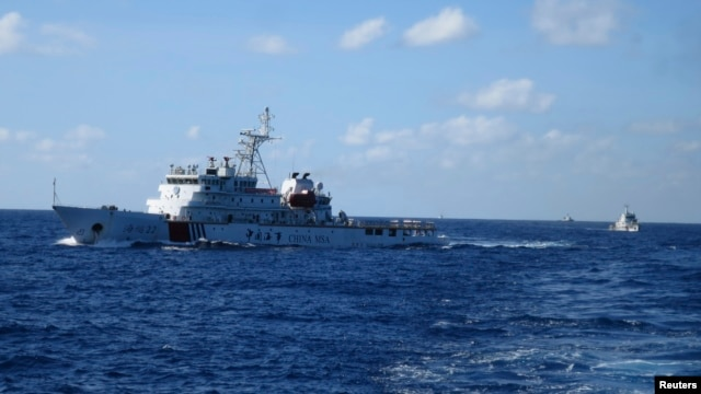 FILE - Chinese ships chase Vietnamese vessels, not shown, after they came within 10 nautical miles of a Chinese oil rig in the South China Sea, July 15, 2014. China has said that the sea holds 130 billion barrels of oil.