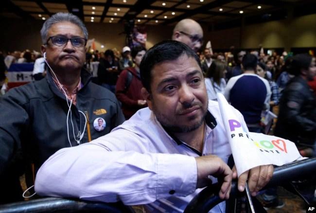 Partidarios del candidato presidencial colombiano Gustavo Petro, obsrevan los resultados del balotaje que le dio la victoria a Iván Duque en Bogotá, el domingo, 17 de junio de 2018.