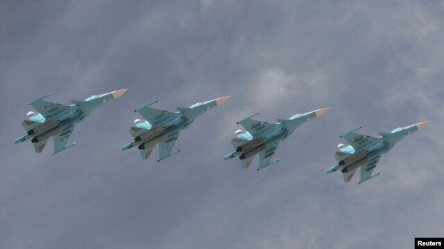 FILE - Sukhoi Su-34 Fullback tactical bombers fly in formation over the Red Square during the Victory Day parade in Moscow, Russia, May 9, 2015.