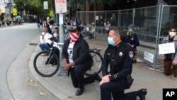 Der Polizeichef Andy Mills (rechts) und der Bürgermeister von Santa Cruz, Justin Cummings (Mitte), knien am 30. Mai 2020 auf der Pacific Avenue in der Innenstadt von Santa Cruz, Kalifornien, um die Erinnerung an George Floyd zu ehren .