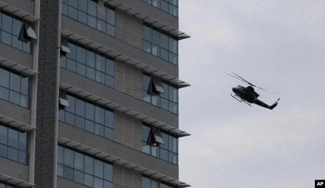 Un helicóptero de la fuerza aérea de Sri Lanka vuela sobre un edificio donde se sospecha se esconden militantes después de un tiroteo en Colombo, Sri Lanka, relacionado con los ataques a iglesias y hoteles el domingo 21 de abril de 2019.