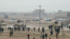 FILE: Protesters throw stones at Iraqi security forces during an anti-government demonstration in Falluja, Iraq, January 25, 2013.