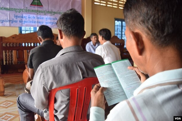 A member of the Grassroots Democratic Party (GDP) read the leaflet shared during the party meeting. The leaflet briefly describes the party policies, including a pathway for rural development, Takeo province, August 9, 2016. (S. Khan for VOA)