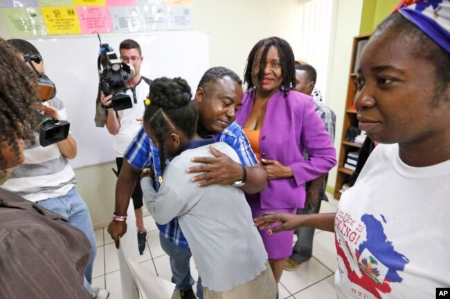 Pierrot Mervilier hugs an unidentified girl whose family, covered by TPS, met with news media in Miami, May 22, 2017.