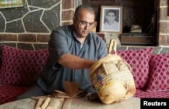Khalid Aaroud, profesor peneliti dan aktivis masyarakat sipil, menunjukkan manuskrip yang diawetkan di rumahnya di desa Ait Mimoune, 9 Juni 2021. (REUTERS/Abdelhak Balhak)