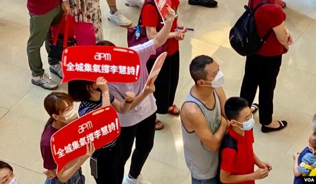 在观塘一个商场观看奥运电视直播的市民手持标语,支持香港单车选手李慧诗。 (美国之音/汤惠芸)