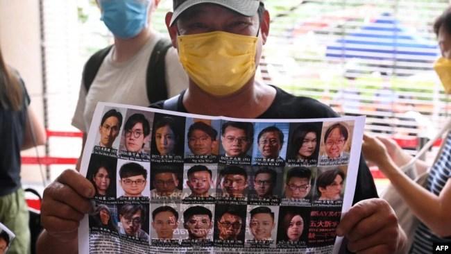 香港民众手举47位泛民派活动人士的照片表示支持。(2021年5月31日)