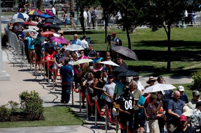 Estadounidenses se resguardan del sol con sombrillas mientras aguardan en fila para presentar sus respetos al fallecido senador John McCain en Phoenix, Arizona, el miércoles, 29 de agosto de 2018.