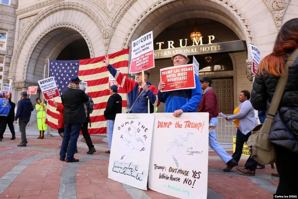 """在华盛顿,在川普新开张的豪华酒店前面,有数以百计的人示威。有人手持标语""""抛弃川普""""""""不让川普进白宫"""""""