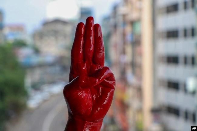 一名反军事政变抗议者用红漆染红的手举手行三指礼。(2021年4月6日)