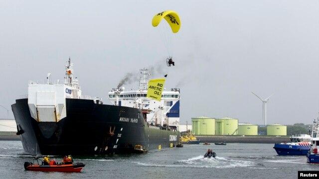Một thành viên của Greenpeace trên chiếc dù lượn mang theo tấm biểu ngữ viết 'No Arctic Oil' (tạm dịch: Không khoan dầu ở Bắc Băng Dương) bay trên đầu chiếc tàu chờ dầu của Nga Mikhail Ulyanov ở cảng Rotterdam. '