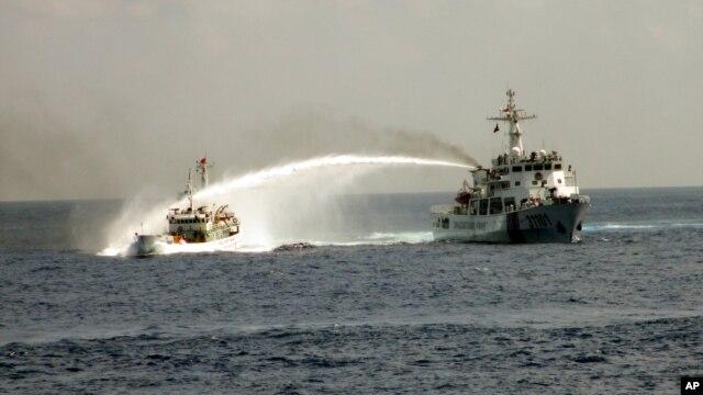 Tàu Trung Quốc (phải) dùng vòi rồng phun thẳng vào tàu Việt Nam. (Ảnh do Cảnh sát biển Việt Nam công bố ngày 4/5/2014).
