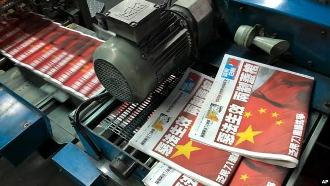 """备受争议的《香港国安法》于2020年7月1日实施,当天出版的《苹果日报》头版以""""恶法生效 两制盖棺""""为题。(资料照:美联社)"""