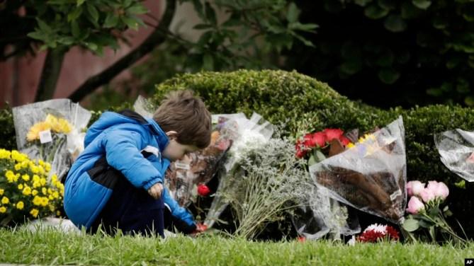 Một cậu bé đặt hoa tưởng niệm các nạn nhân hôm 28/10.
