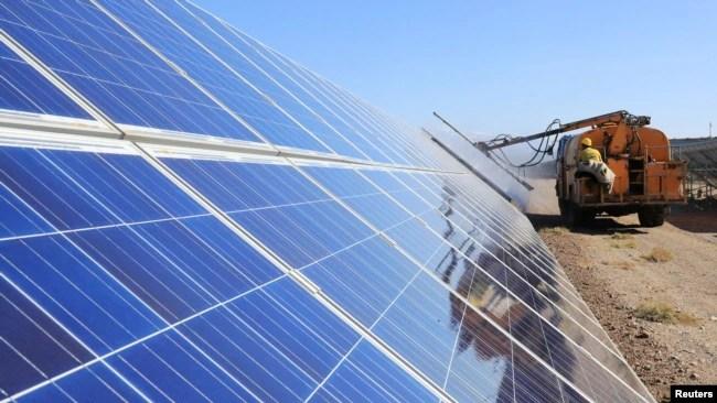 资料照片 - 2018 年 10 月 22 日,一名工人在中国新疆维吾尔自治区哈密市的一个光伏工业园区操作机器清洁太阳能电池板。