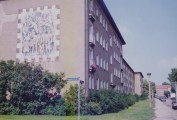 """Spartan apartment block typical of WK I, here with a ceramic mural """"Socialist Life"""", the first such artwork created in the new town (photo: author, 1996)."""