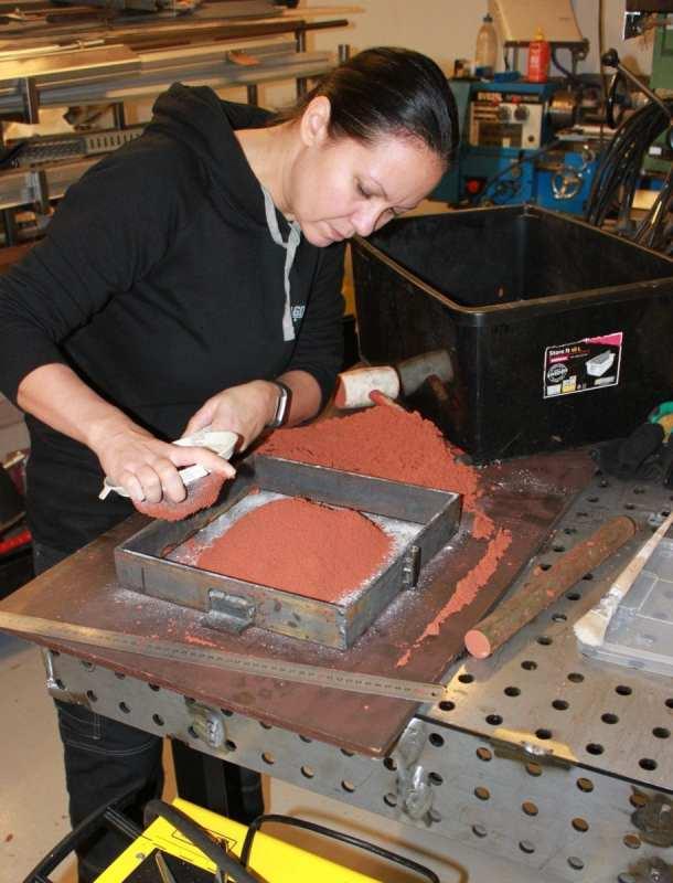 Gjuta metall i sand: Finfördela sanden med en sil över avgjutningsformen.