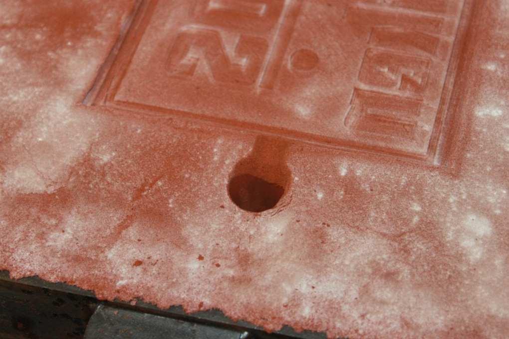 Smälta metall i sand: Närbild på feeder hålet.
