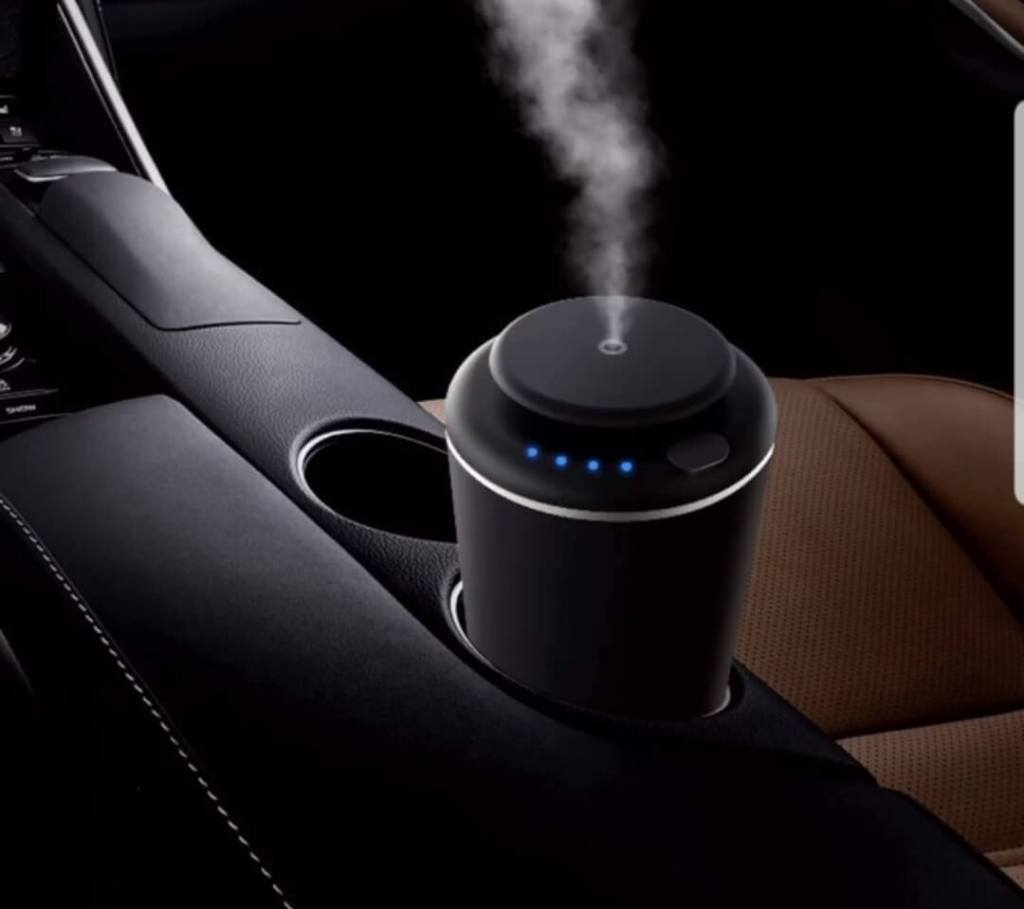 The TMS F1 Black Aroma Diffuser sitting in a car's cupholder.
