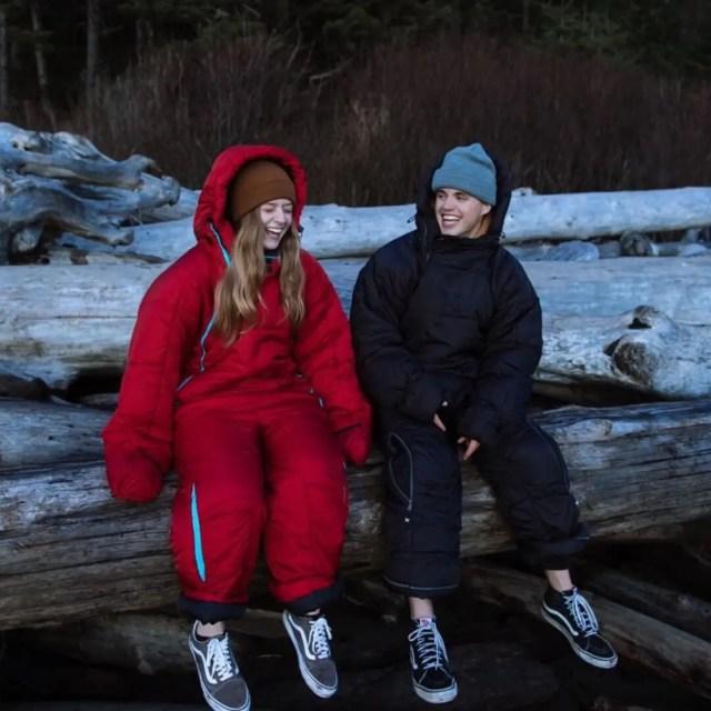 Two people sitting on a log wearing their Selk'bag sleeping bags.