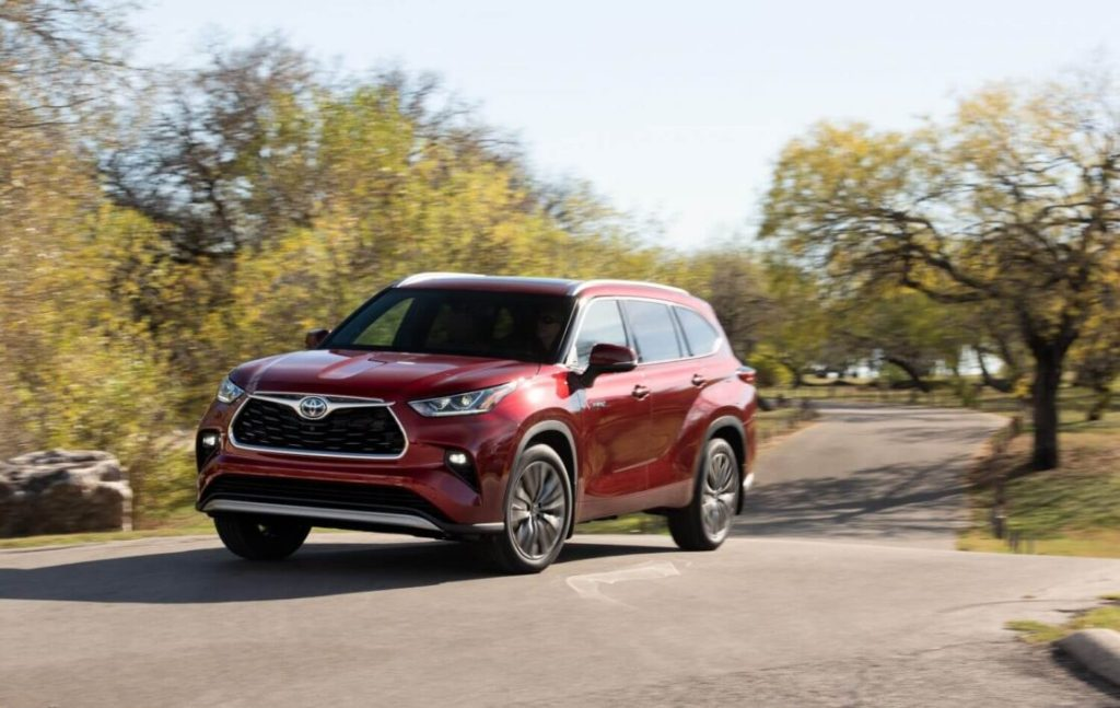 The 2021 Toyota Highlander driving on a windy, paved road with trees on either side.