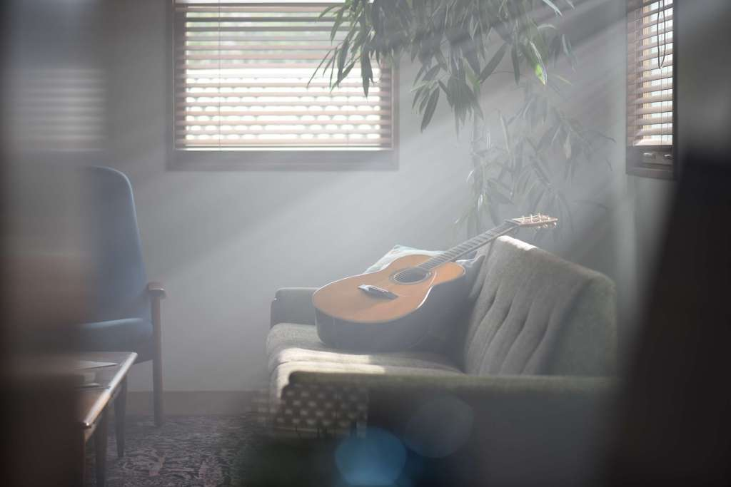 The Yamaha LS-TA TransAcoustic guitar bathed in sunlight on a couch.