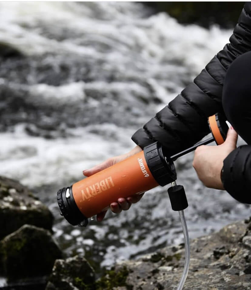 Someone using the LifeSaver liberty bottle to pump water into it and purify the water from the stream.