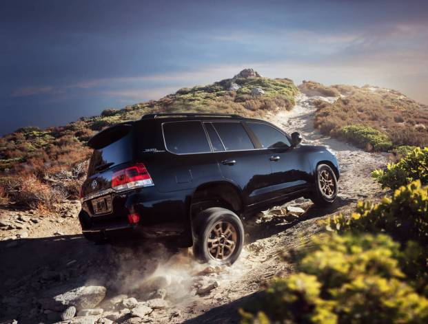 The black 2021 Toyota Land Cruiser Heritage Edition scaling a rocky mountainous path.