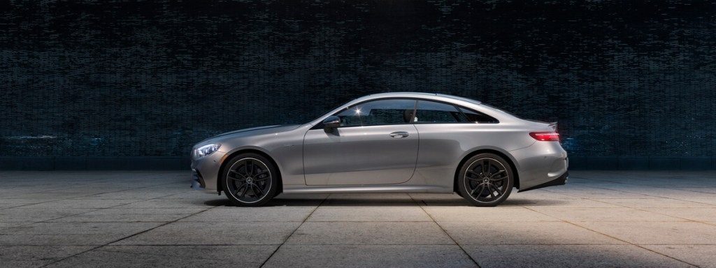 A silver 2021 Mercedes-Benz E 450 AMG Coupe, which contains the new heat map feature that all these vehicles can brag about, on a paved area in the dark.
